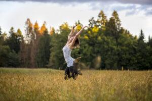 donna felice che salta delice in un campo