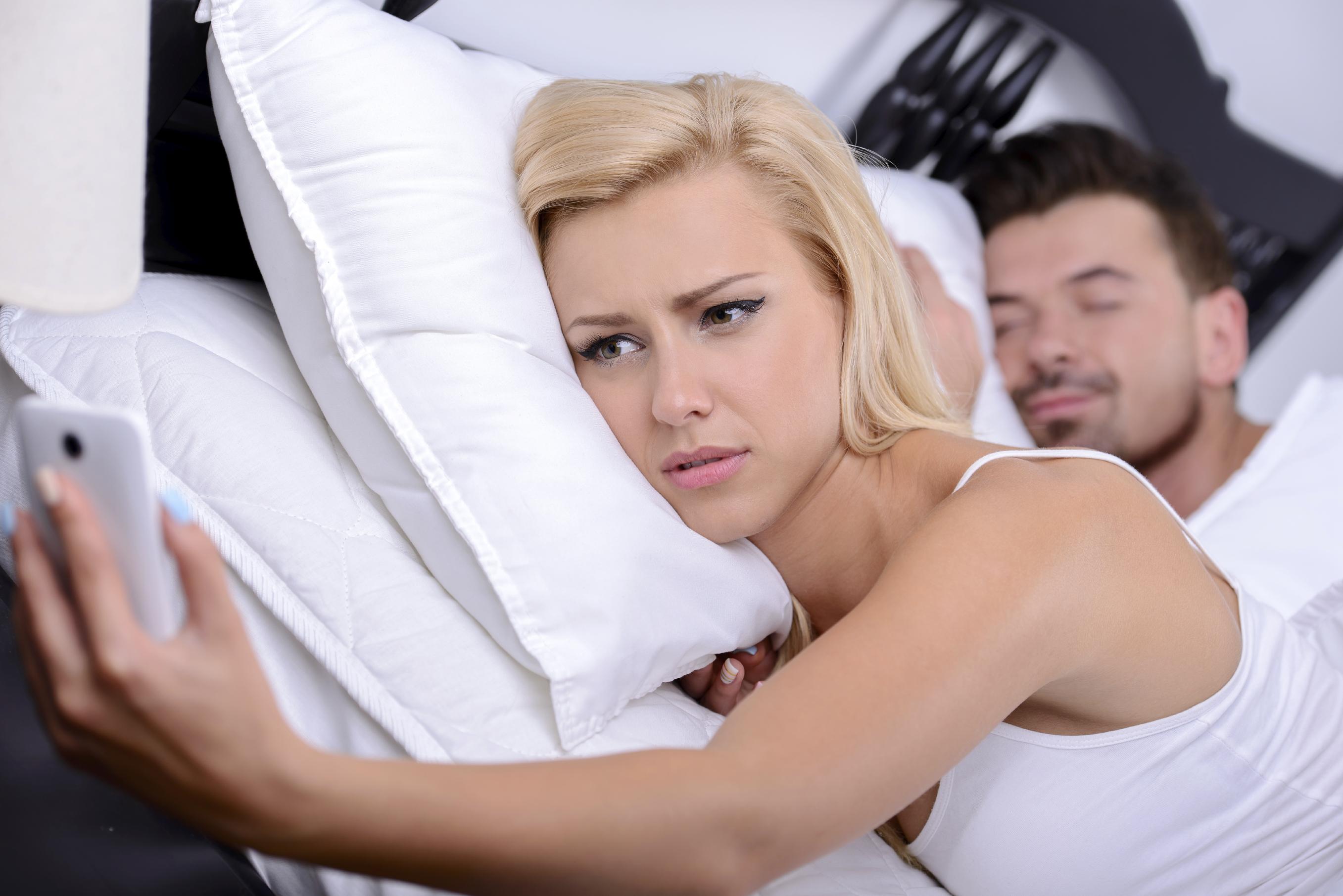 donna che a letto mentre il marito dorme guarda il cellulare