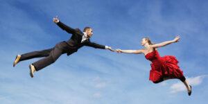 uomo e donna che si danno una mano volando in cielo
