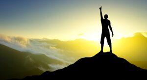 uomo con la mano alzata sopra la vetta di una montagna