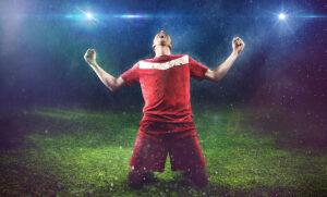 sportivo che esulta in ginocchio con gli occhi al cielo