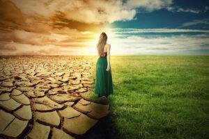 donna che attraversa un terreno diviso tra fertilità e aridità