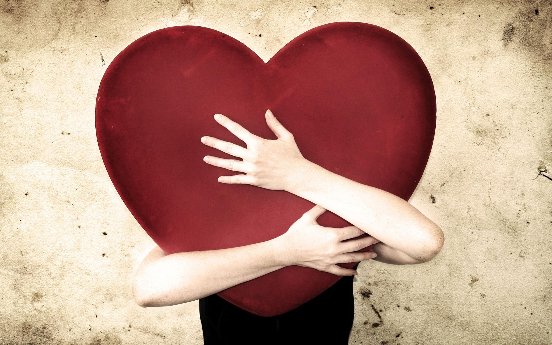 donna che abbraccia un cuore grandissimo