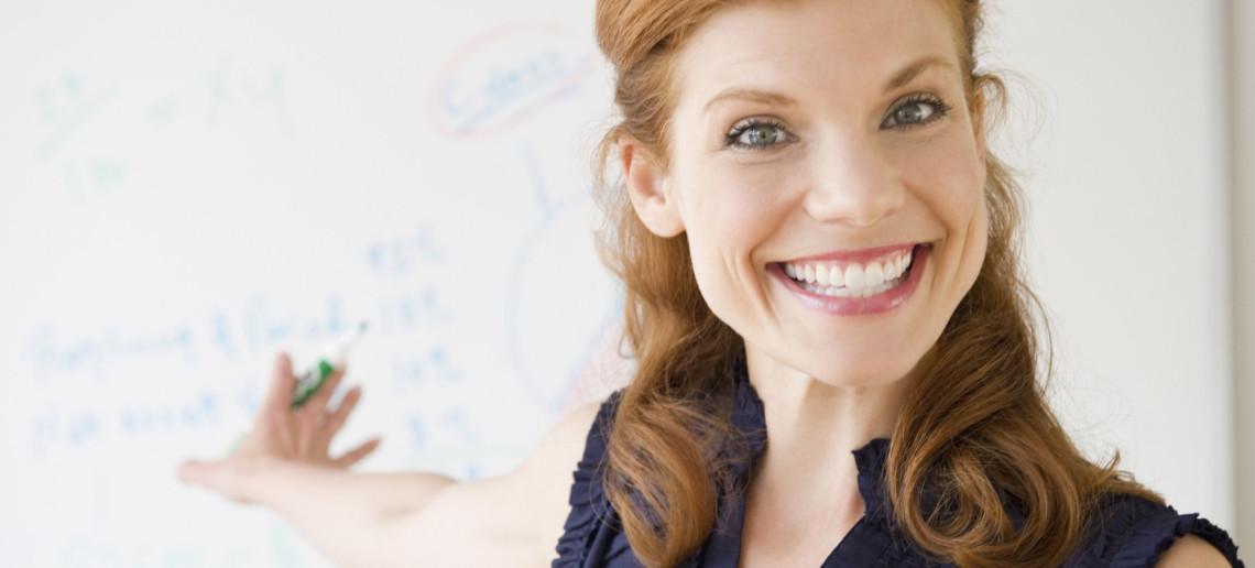donna che sorride mentre scrive alla lavagna